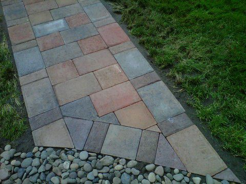 Paver pathway leading to gravel. Made with multiple shades of red, brown, and grey. Mowed lawn on either side.