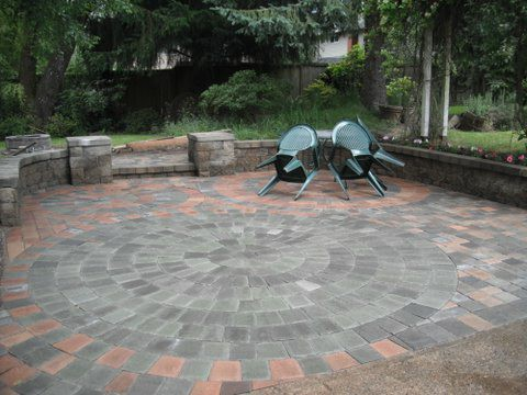 Rounded paver patio shape. Made with different shades of red, brown, and grey pavers. Small table and two chair to the right. Wall encompassing the patio.