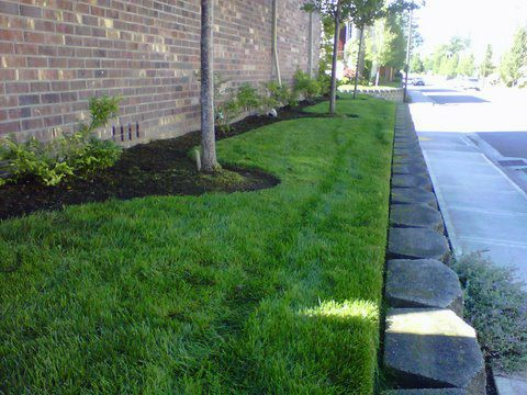 Modern Landscaping work. Perfectly cut grass on side of building with small retaining wall next to the sidewalk.