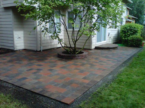Multiple shades of grey, brown, and red pavers added on patio in the back of a house to gain more usable space while enhancing the look of the back yard.