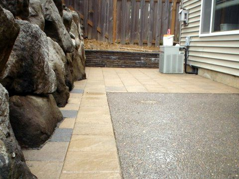 On the left is a retaining wall made out of natural rocks. Wooden fence in the back. Floor between house and wall made out of tan and grey pavers.