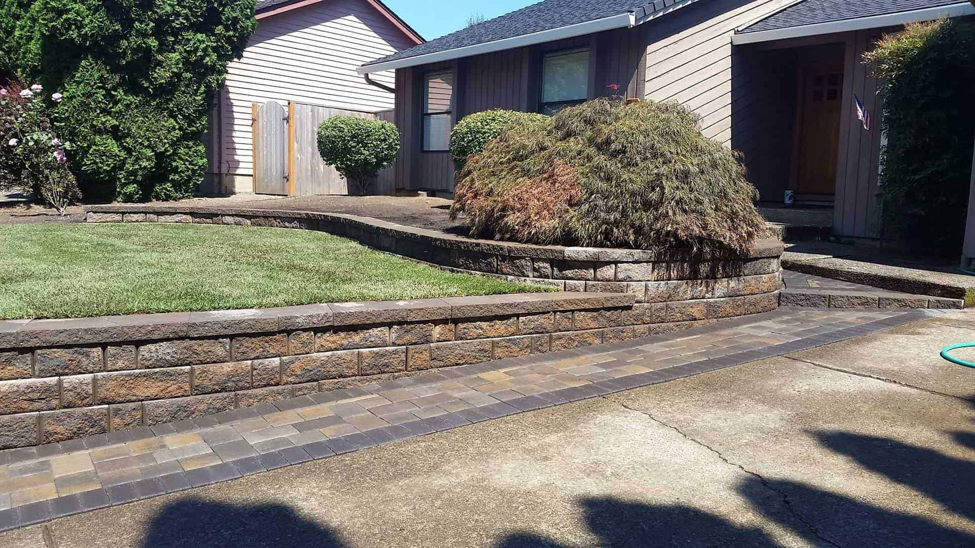 Retaining walls made out of brick pavers or natural stone with pathway and small trees trimmed and lawn maintained Pavers in POrtland