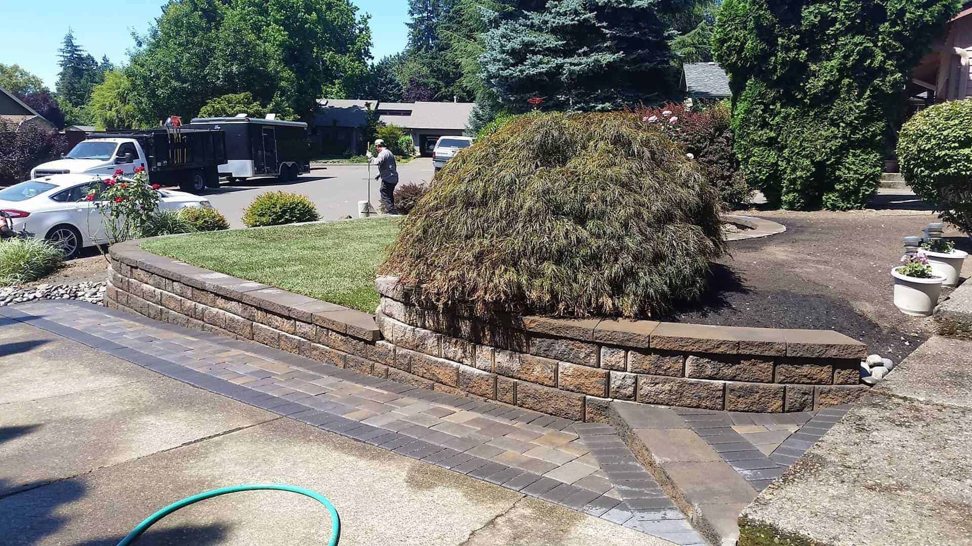 Retaining wall made out of brick pavers or natural stone with pathway and small trees trimmed and lawn maintained
