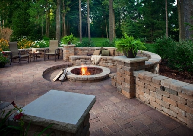 Garcias Landscaping Beaverton, Beautiful backyard with round shaped brick pavers in Portland and Retaining walls and stone retaining wall with fire pit in the middle
