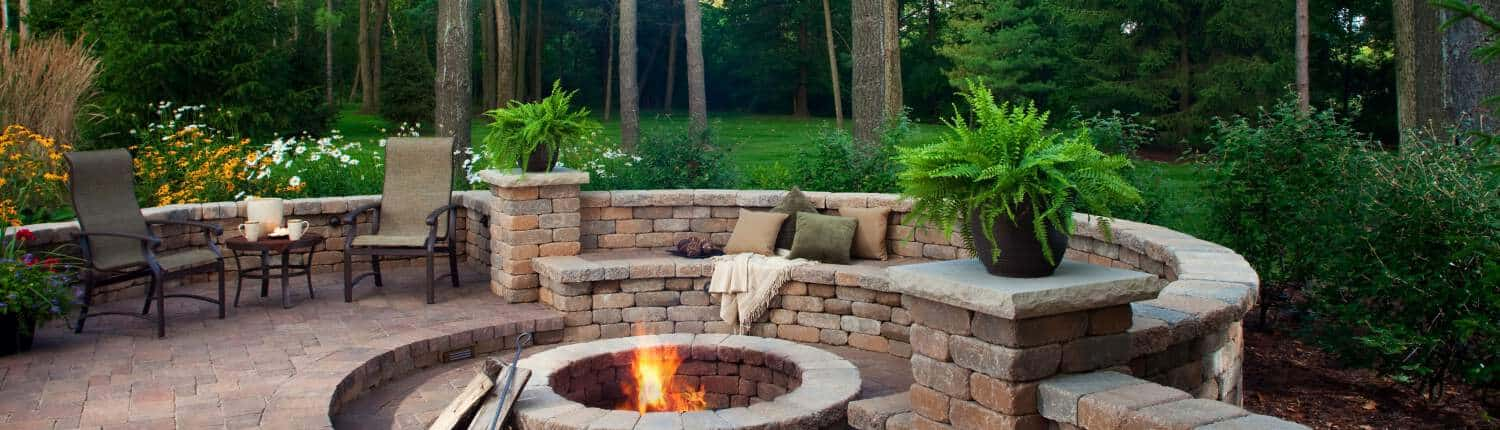 Garcias Landscaping Beaverton, Beautiful backyard with round shaped brick pavers and stone retaining wall with fire pit in the middle