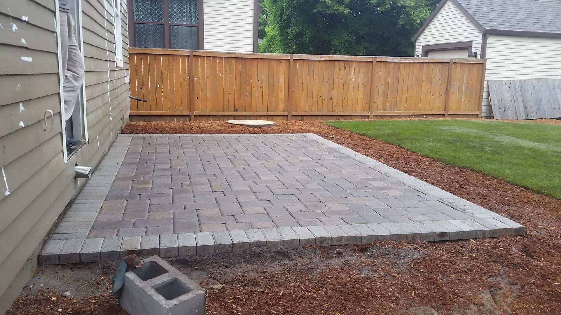 Back patio made out of grey and light brick concrete pavers. Perfectly alined forming an aesthetically pleasing square pattern.