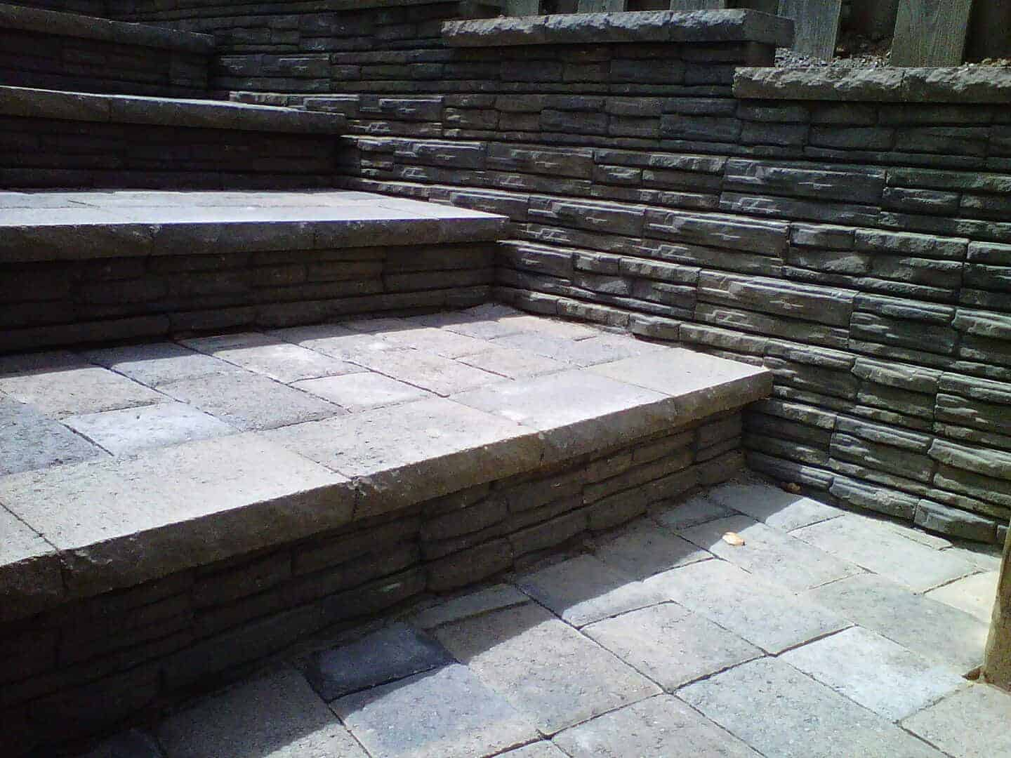 small set of grey stairs made out of concrete brick pavers. in Portland Paver patio, paver patio floor with retaining walls on the right side