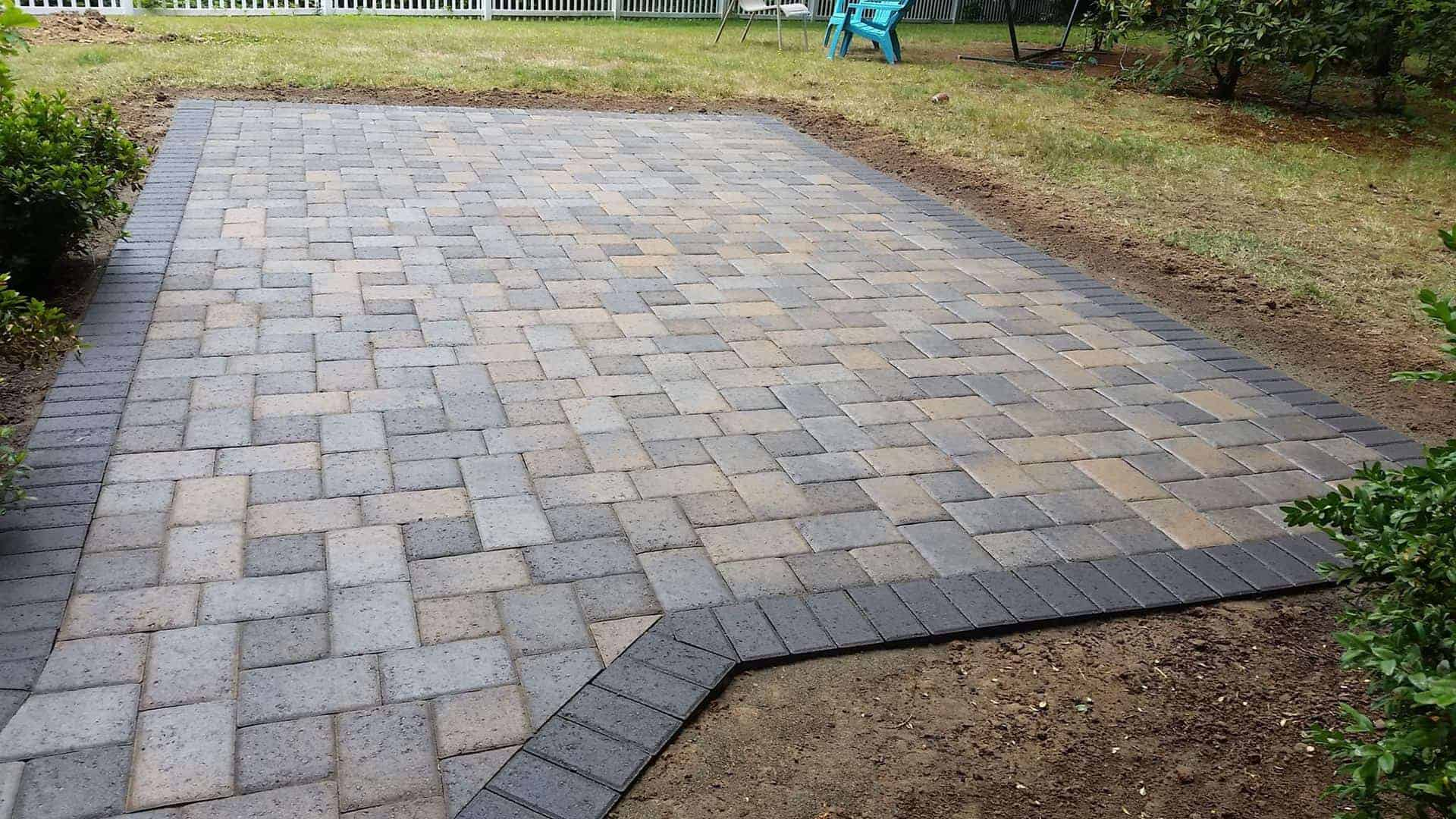 Brick tan and gray paver patio floor with dark gray trimming all around