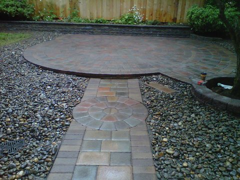 Rounded paver patio shape with pathway attached. Made with different shades of red, brown, and grey pavers. Surrounded by gravel. Wooden fence in the back.