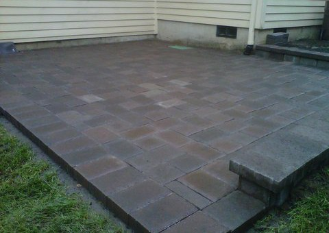 Back patio made out of grey and brown and light brick concrete pavers. Perfectly aligned forming an aesthetically pleasing square pattern.