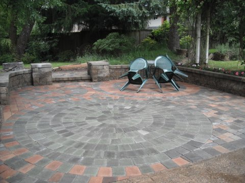 rounded brawn grey brick paver patio floor with area for outdoor furniture.